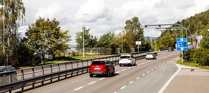 biler kjører på en vei ved en bomstasjon